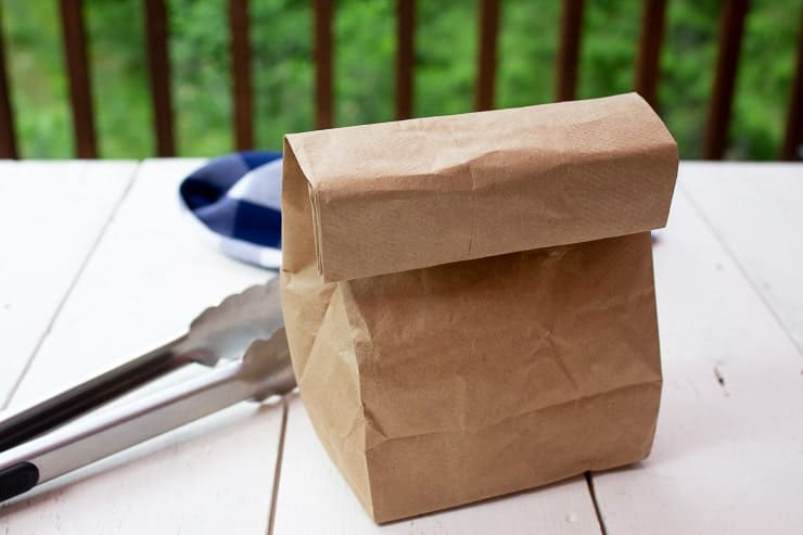 A paper bag on a white board with a a pair of tongs next to the bag.