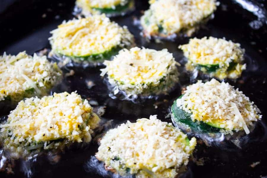 Breaded zucchini in a pan with hot oil.