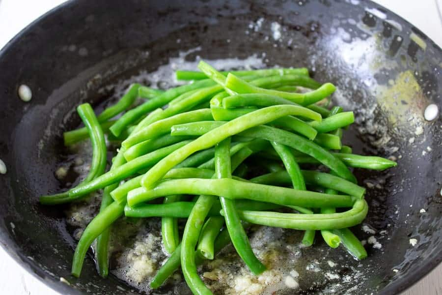 Green beans in a saute pan with butter and garlic.