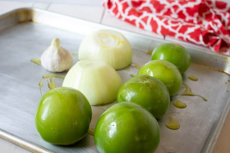 A baking tray with tomatillos, onions and garlic.