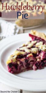 A slice of berry pie on a white plate with a whole pie behind the slice.