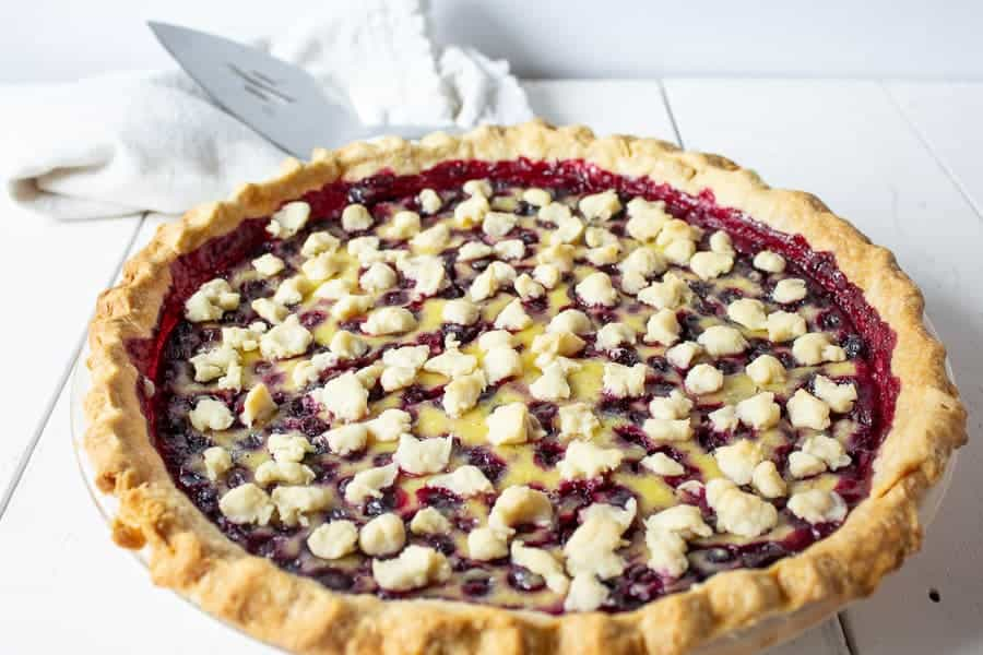 A whole huckleberry pie on a white board.