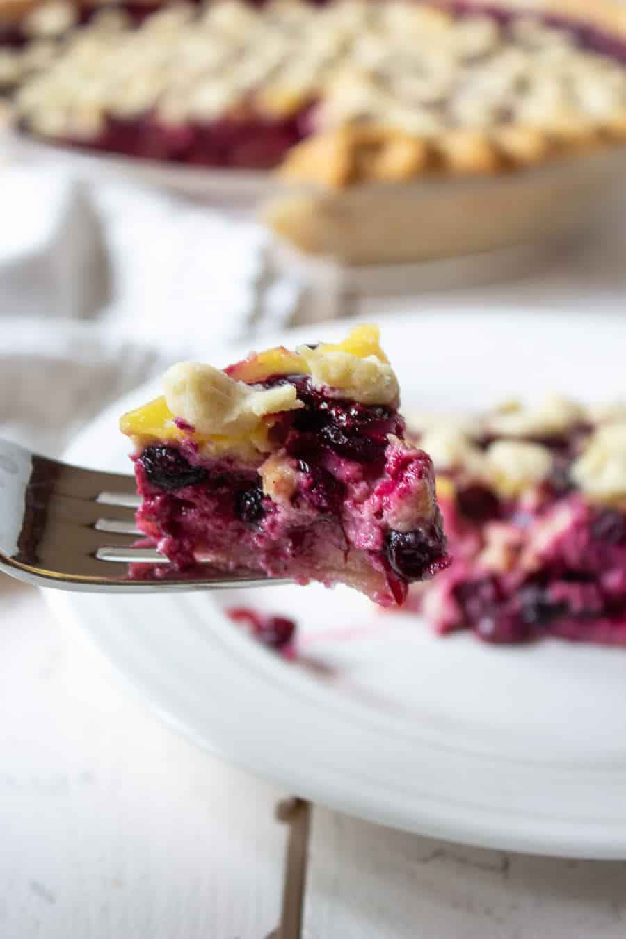 A fork with a bite of huckleberry pie.
