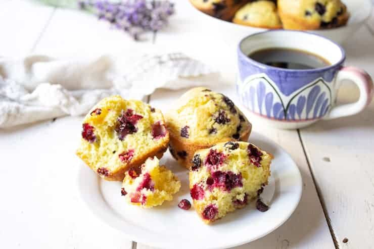 A plate of huckleberry muffins with one muffin split in half.