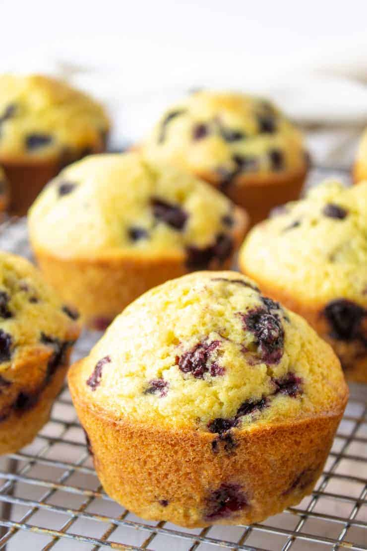 Muffins with berries on a baking rack.