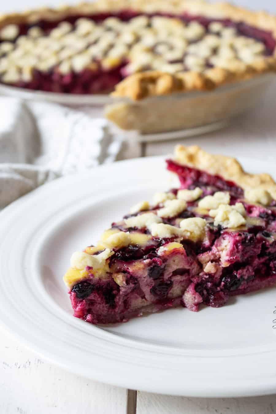 Slice of berry pie on a white plate with the whole pie behind the slice of pie.