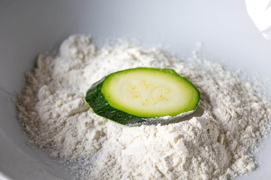 A zucchini slice in a bowl of flour.