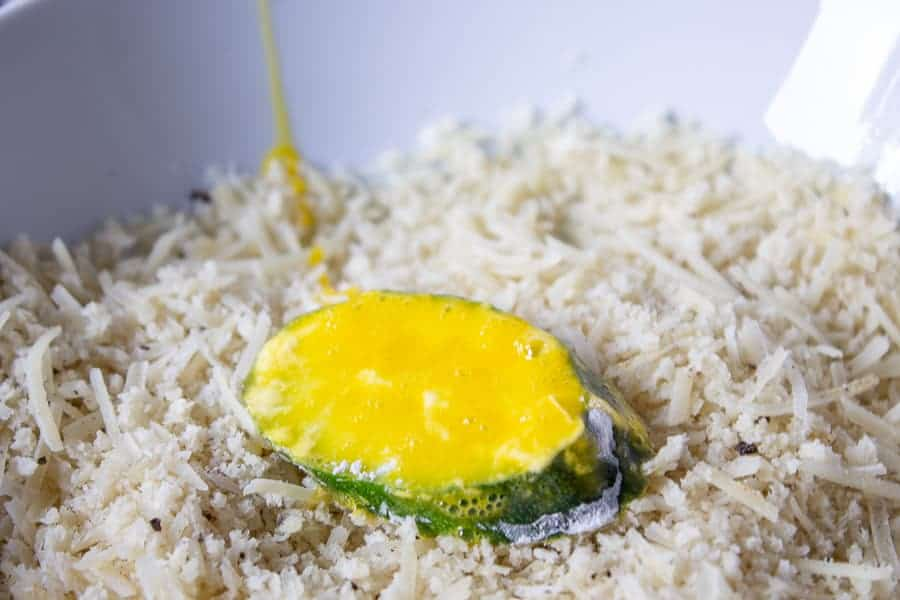 Zucchini slice covered with egg in a bowl with a breading mixture.
