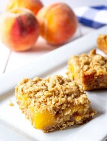 Peach Crumb Bars on a white late with fresh peaches in the background.