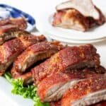 Grilled ribs on a white plate lined with lettuce leaves.
