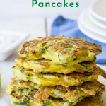 A stack of zucchini pancakes on a white board.