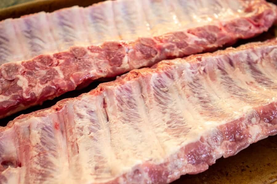 Baby back ribs with bone side up on a baking sheet.