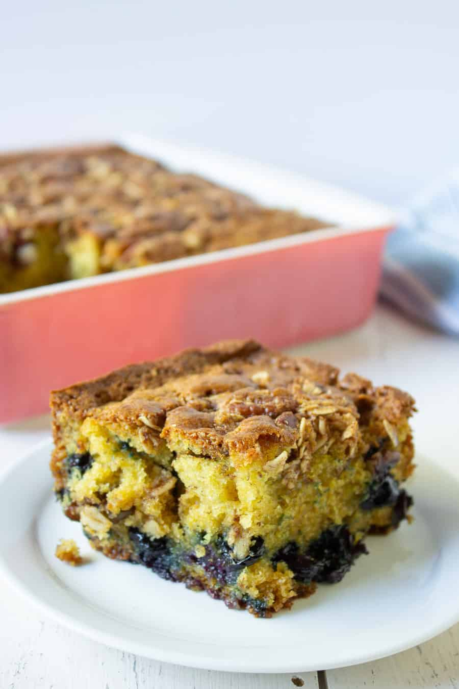 A slice of yellow cake with blueberries and pecans on a small plate.