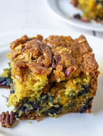 A wedge of coffee cake filled with blueberries and topped with pecans.