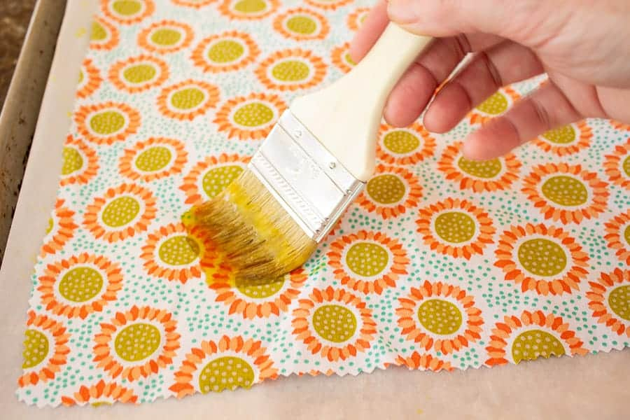 A disposable paintbrush brushing melted wax onto fabric.