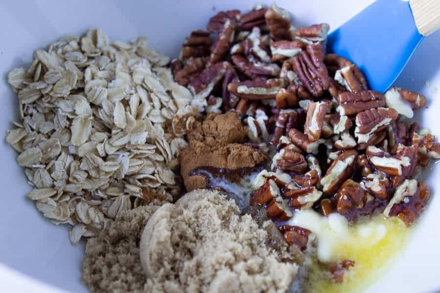 Chopped pecans, oatmeal, brown sugar and melted butter in a bowl.