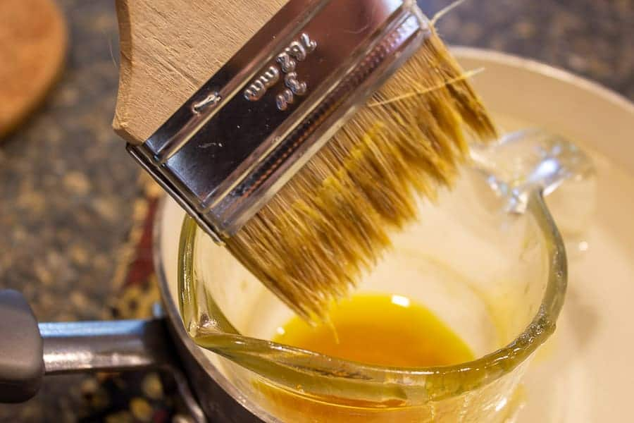A disposable paint brush dipping into a wax mixture.