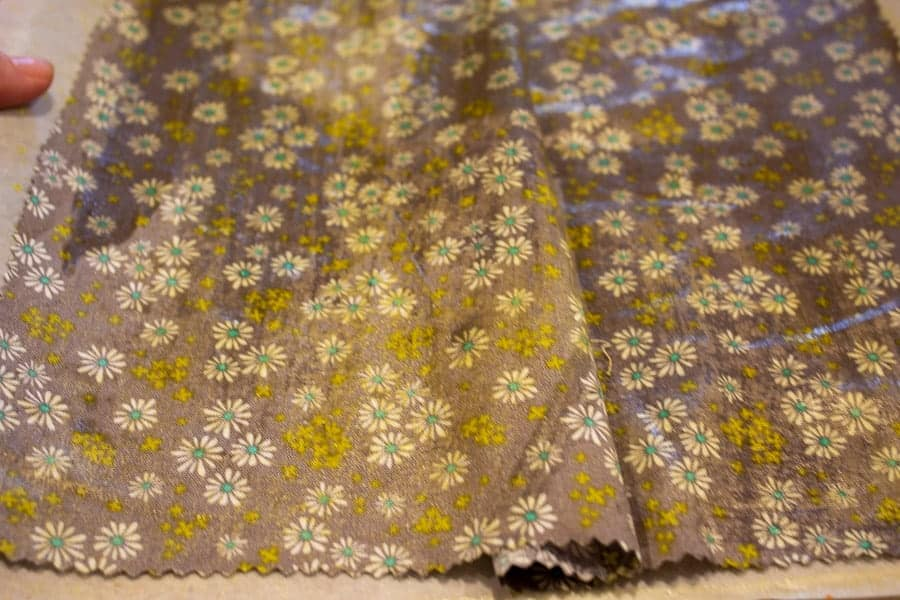 Floral fabric covered with beeswax on a baking sheet.