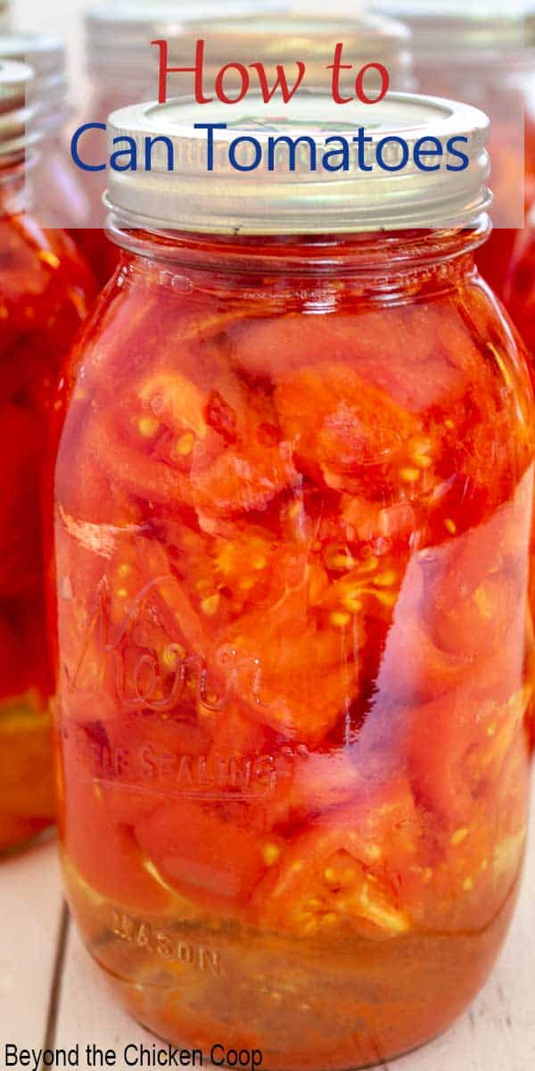 A quart sized canning jar filled with chopped tomatoes.