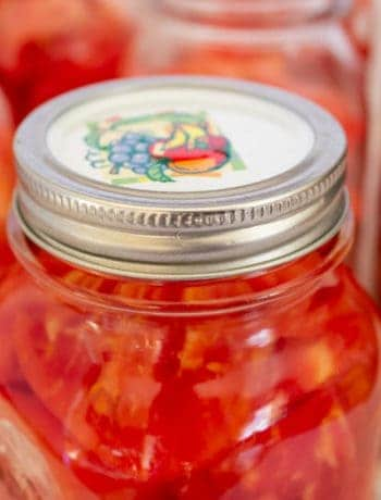 A canning jar filed with chopped tomatoes.