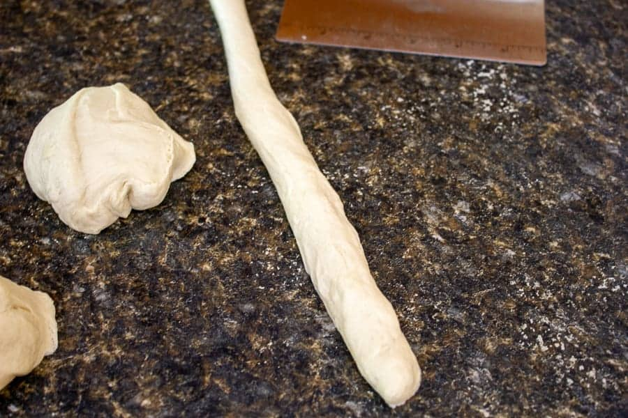 A long rope of pretzel dough on a counter.