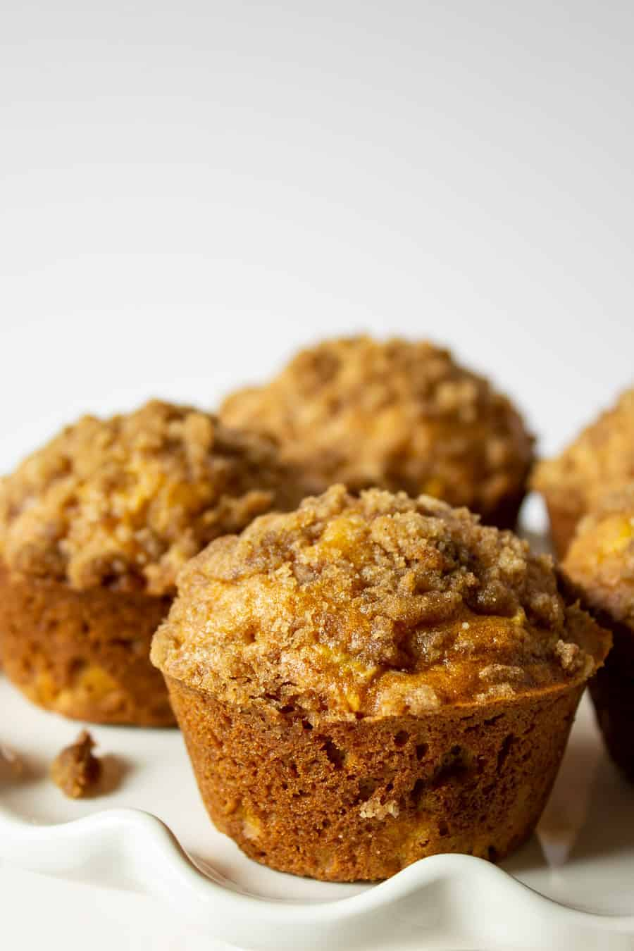 Pumpkin apple muffins on a white plate.