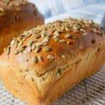 A loaf of bread topped with seeds sitting on a baking rack.