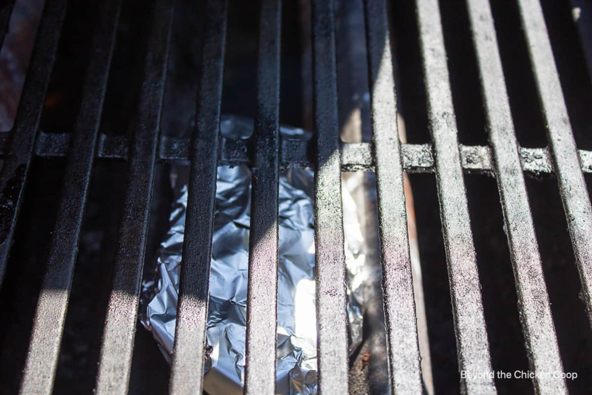 A gas grill with a foil packet below the grate.