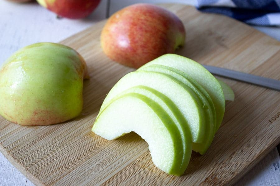 Slices of a green apple on a cutting board.