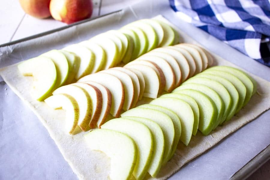 Fresh apple slices lined up in three rows on top of puff pastry.