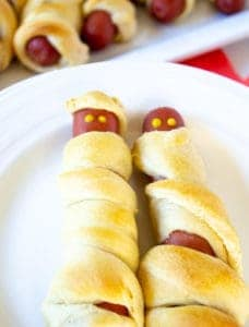 Hot dog mummies on a white plate.