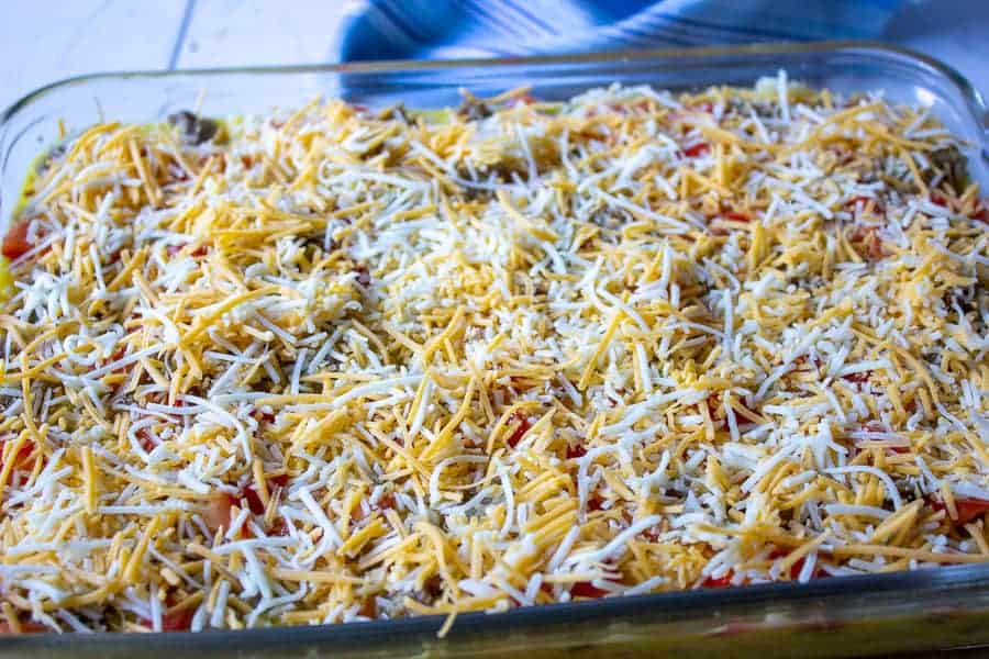 Grated cheese on top of an egg mixture.