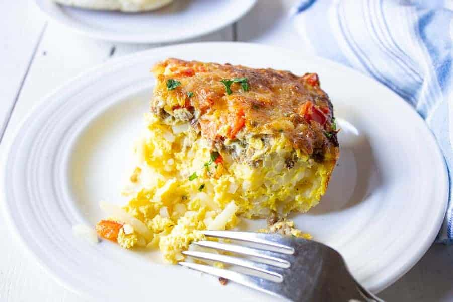 A breakfast casserole filled with eggs, hash browns and sausage on a white plate with a fork.