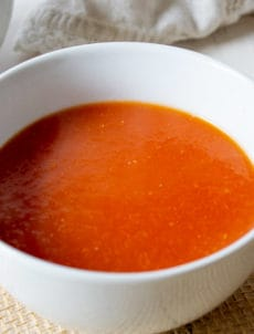 Tomato soup served in a white bowl.