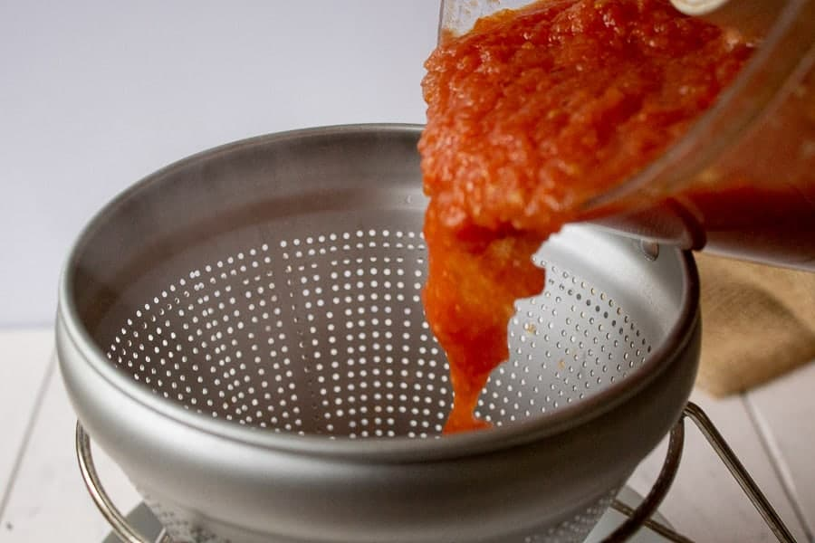 Tomato sauce being poured into a food mill.