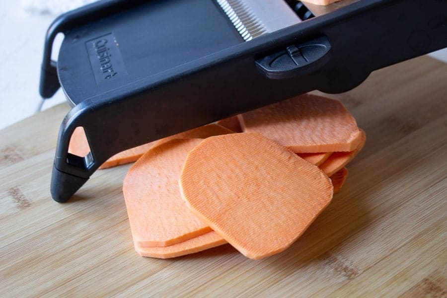 Sweet potatoes being cut on a mandoline.