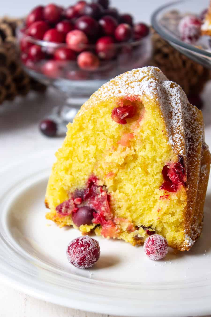 A slice of bundt cake filled with fresh cranberries and decorated with sugared cranberries.
