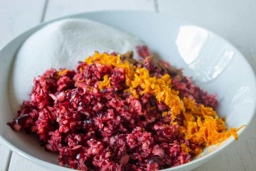 A bowl filled with fresh chopped cranberries, orange zest and cinnamon.