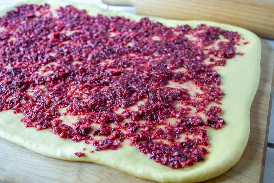 Chopped cranberries on bread dough.