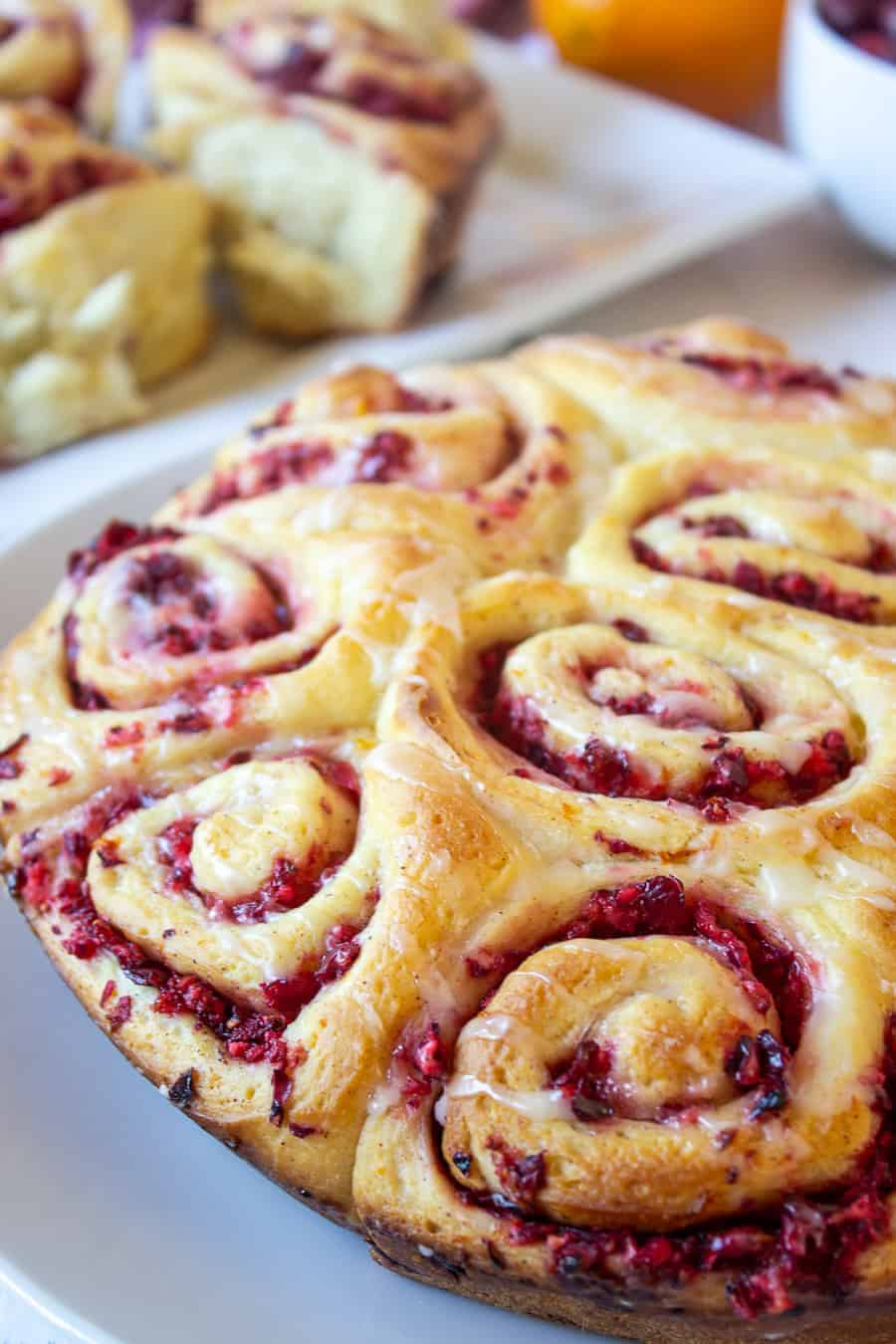 A plateful of freshly baked cinnamon rolls filled with chopped cranberries.