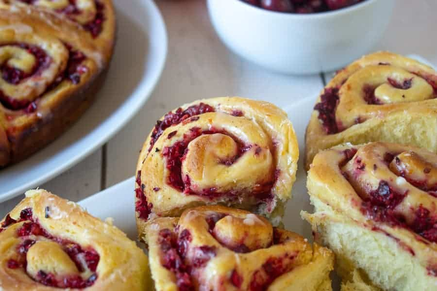 A white plate with cranberry sweet rolls.