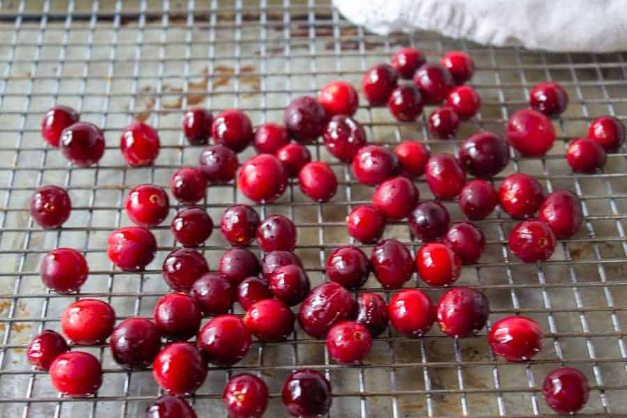 Shinny cranberries drying on a baking rack.