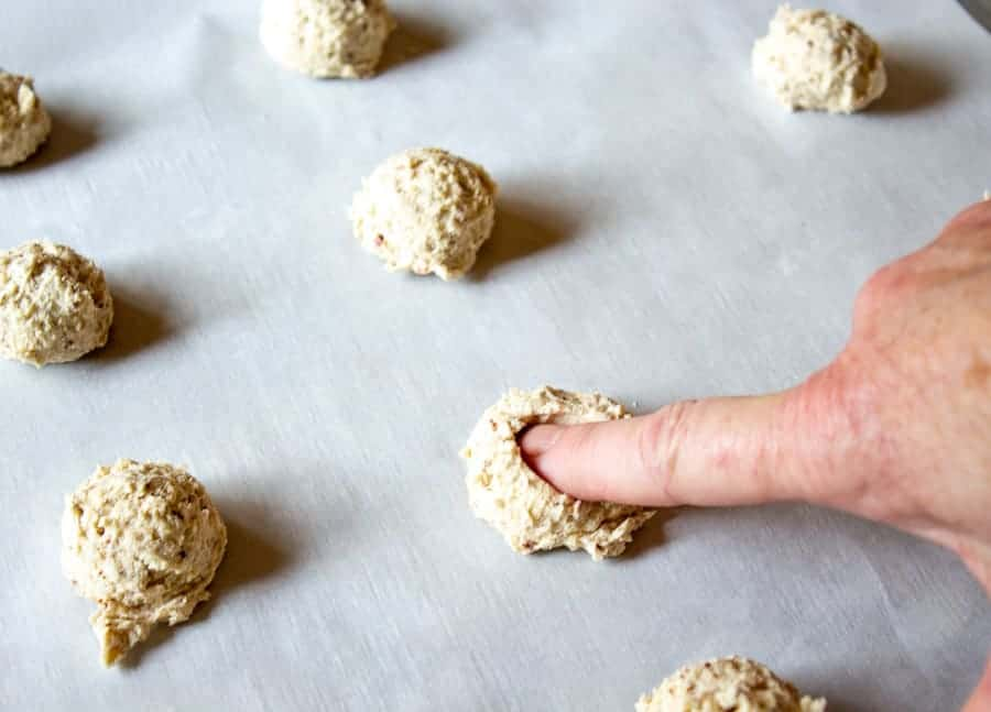 Pushing down on a round mound of cookie dough.