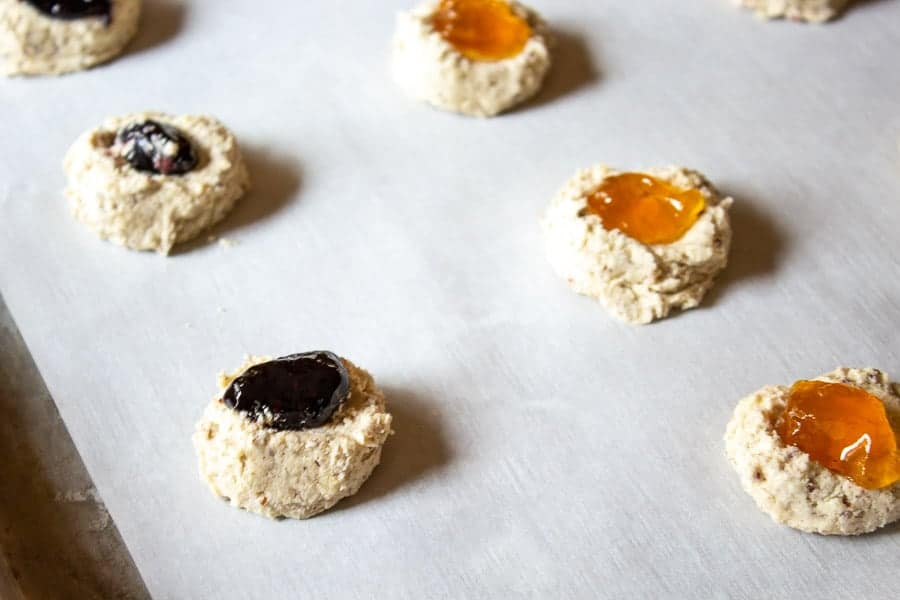 Thumbprint Cookies filled with jam on a baking sheet.
