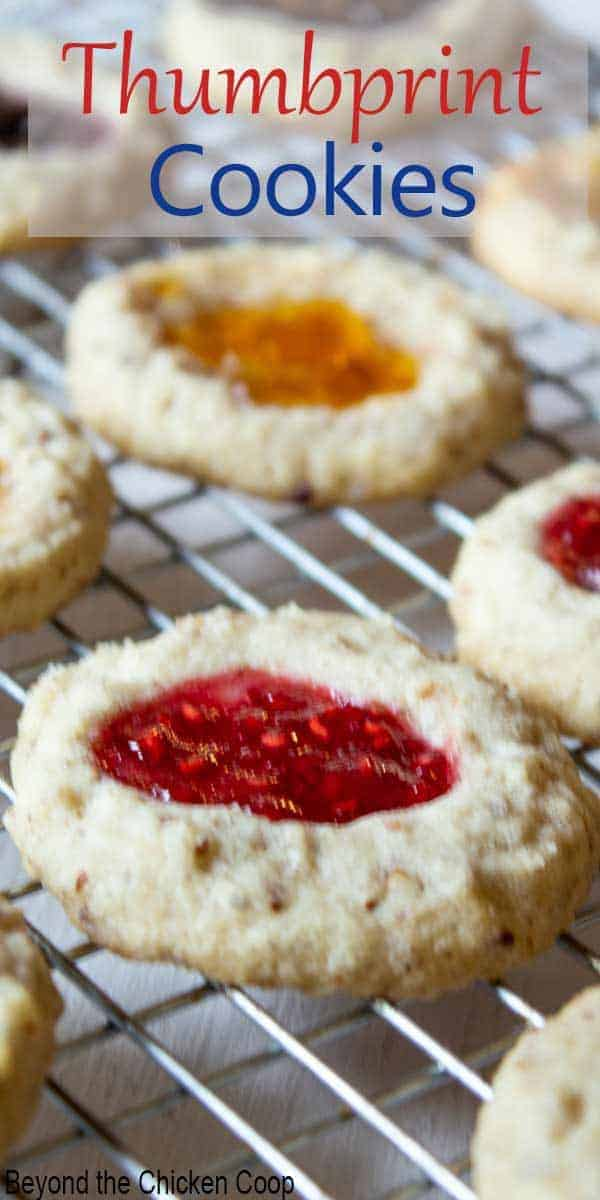 Jam filled cookies on a baking rack.