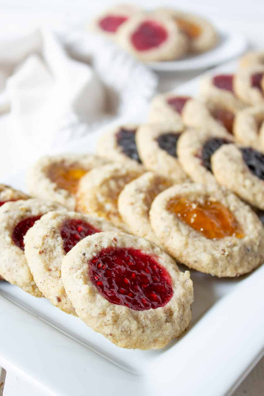 A white platter filled with cookies with different types of jam baked into the cookies.