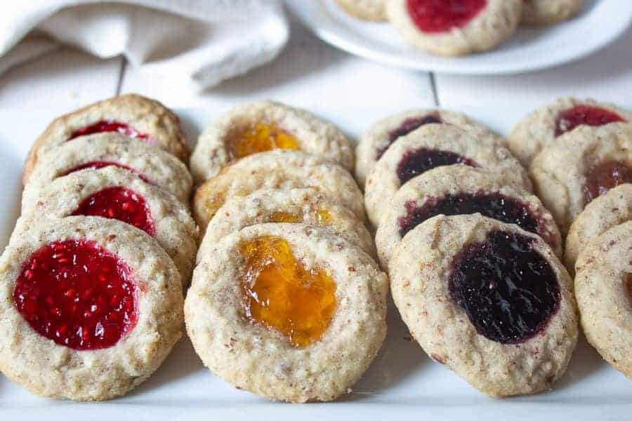Thumbprint cookies with different types of jam on a white plate.