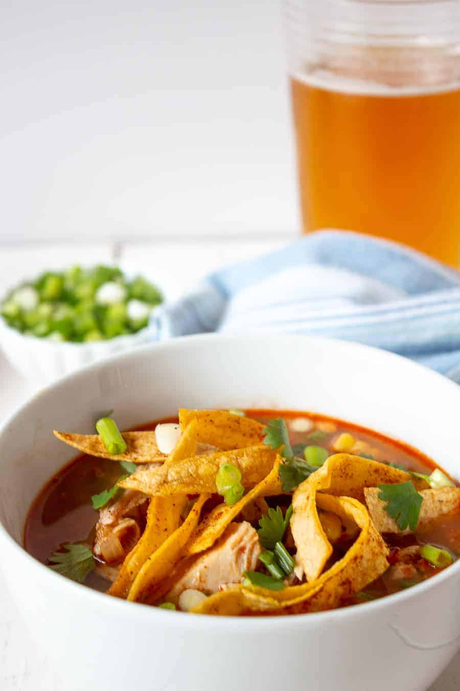 A bowl of turkey tortilla soup topped with crunchy tortilla strips.