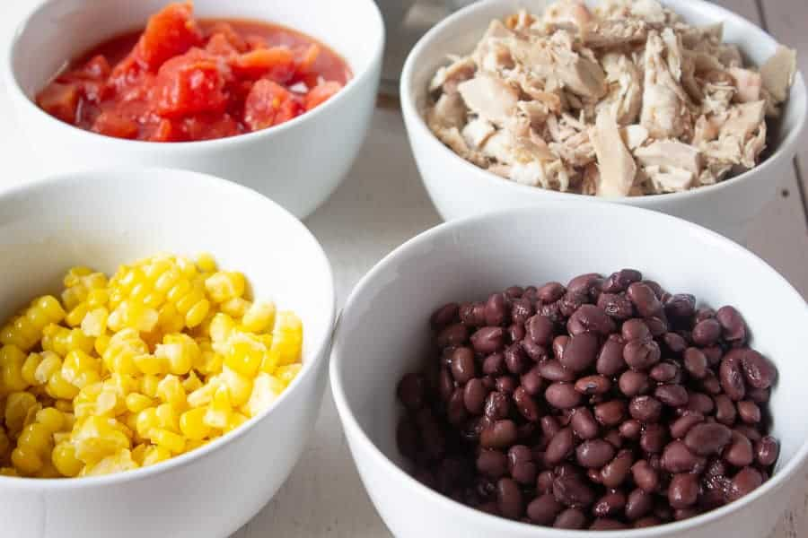Bowls filled with black beans, corn, tomatoes and chopped turkey.