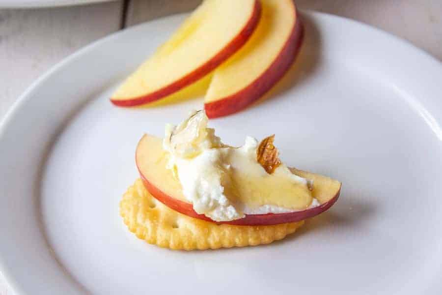 A cracker topped with an apple slice and goat cheese.